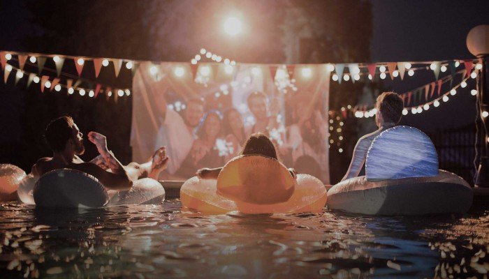 Adults lounging in inner tubes in pool at night screening a movie.